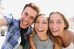 a teen guy and two teen girls smiling and taking a selfie