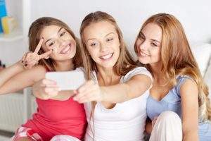 three teen girls smiling and taking a selfie